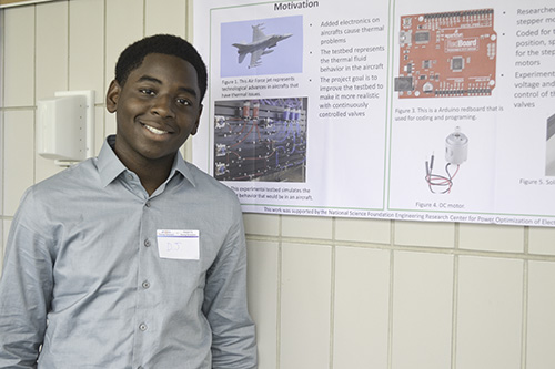 High School student, Darius Jackson, standing by his research poster at the conclusion of the Young Scholar program.